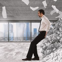 Businessman pushing with fatigue a big pile of paperwork