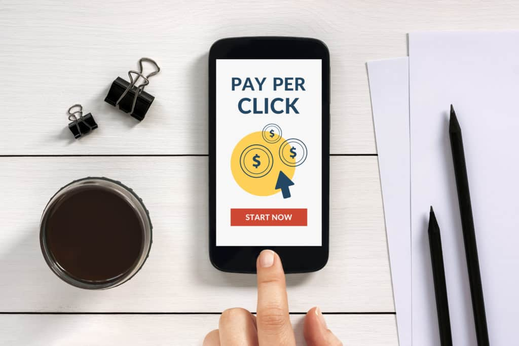 Pay Per Click (PPC) concept on smart phone screen with office objects on white wooden table