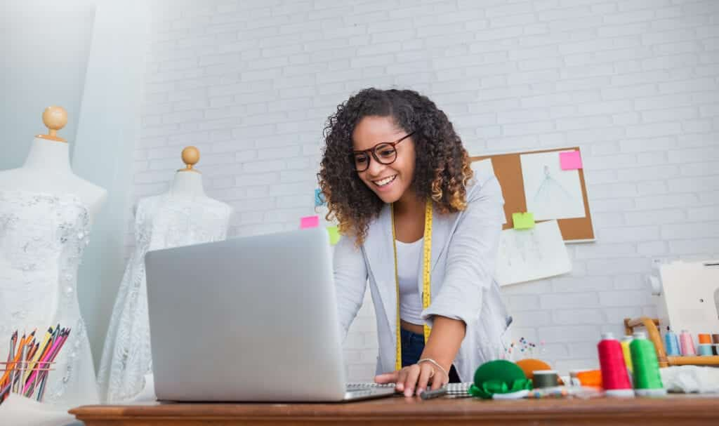 SEO packages for small business means bringing in pros like this smiling woman at a laptop with dresses behind her