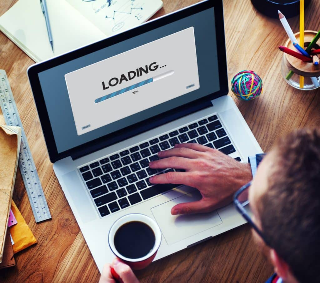A man looking at a loading bar on a laptop and drinking coffee.
