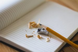 A pencil sharpener, pencil and pencil shavings on a notebook